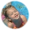Child in wading pool smiling
